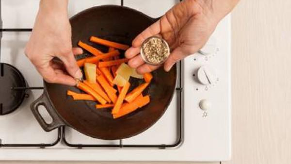 En un wok con un poco de aceite de oliva virgen extra fríe las zanahorias y las patatas con el ajo, agrega las semillas de hinojo y la pastilla de caldo desmenuzada, añade un vaso de agua y cuece dura