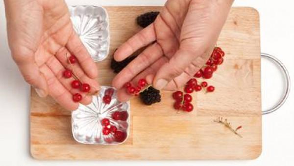 Lava la fruta, las pasas granuladas y repártelo todo en pequeños moldes.