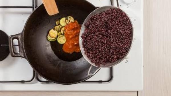 En un wok, saltea el calabacín con 1 cucharada de aceite de oliva. Añade el contenido del tomate frito y mézclalo con la carne picada cocina previamente. Escurre bien el arroz y sazona con la salsa de