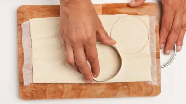 Prepara la masa de pizza siguiendo las instrucciones. Estira la masa en una hoja de unos pocos mm de espesor; colócala sobre papel de horno y corta algunos discos, usando un cortapasta.