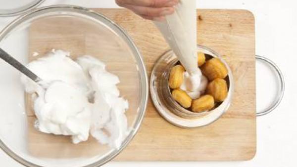 Con la ayuda de unos anillos de pastelería, recúbrelos por dentro con los bizcochos y con una manga pastelera rellénalos de crema.