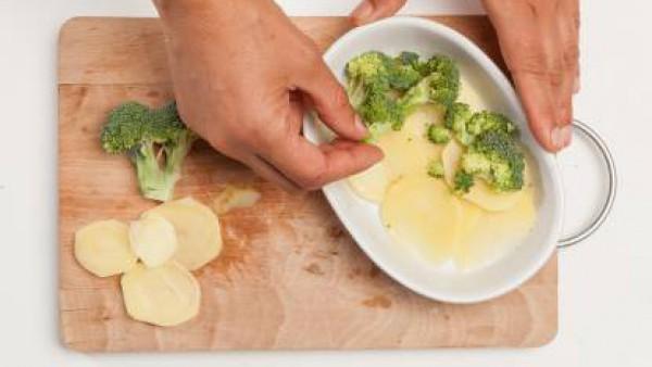 En una fuente de horno untada con un poco de aceite de oliva virgen extra pon una primera capa de patatas, a continuación, cubre con una capa de brócoli y cierra con una segunda capa de patatas.