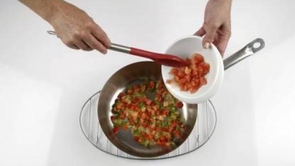 Pon en una cazuela con 2 cucharadas de aceite de oliva, la cebolla, el pimiento verde y el pimiento rojo a sofreír. Cuando haya cogido color, añade el tomate a dados y deja cocer. Reserva el sofrito r