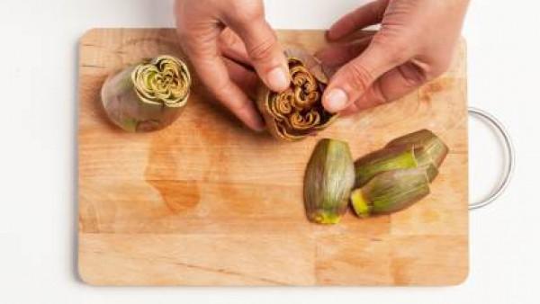 Limpia las alcachofas, quita las hojas exteriores duras y la barba y corta el interior finamente. Por otra parte, limpia la cebolla y pica finamente. En una sartén, rehoga la cebolla y luego añade las