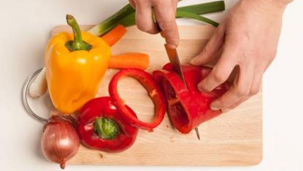 Lavar las verduras; corta en dados los pimientos y zanahorias y pica finamente la cebolla y la cebolleta.