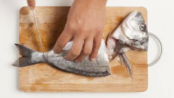 Limpia el pescado, corta las cabezas y colas y, con la ayuda de una tijera, elimina todas las aletas. Rellena el vientre de cada dorada con el diente ajo, romero y Avecrem.