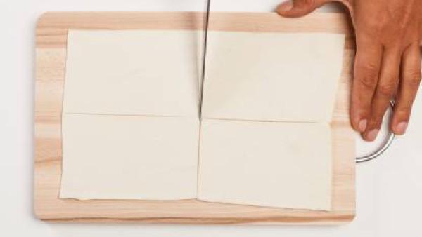 Corta la masa de hojaldre en rectángulos y colocarlos en una bandeja con papel de hornear. Trocea el salmón. Precalienta el horno a 180 °C.