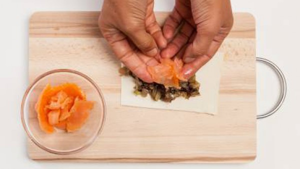 Rellena los hojaldres con un poco de achicoria y unas tiras de salmón. Dobla los rectángulos uniendo dos untas opuestas y dándole forma redondeada. Asegúrate de unir bien los bordes y repite la operac