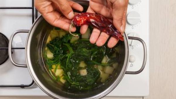 Cocina a fuego lento unos minutos y luego agrega las patatas y cocina unos 25 minutos en una olla tapada. Por último, apaga el fuego, espolvorea con el chile y sirve.