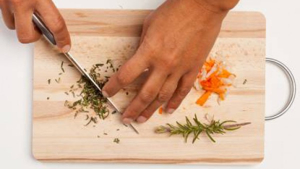 Por otro lado, limpia y pica las zanahorias, la cebolla picada y el romero. En un wok, prepara la salsa con una cucharada de aceite de oliva, la cebolla picada y la zanahoria. A continuación, añade el