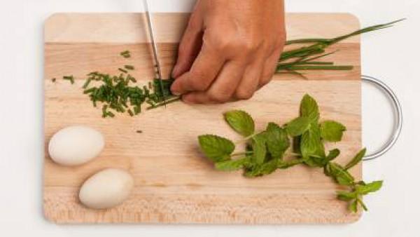 En una tabla de cortar, coloca las hierbas y pícalas finamente. Por separado, prepara el relleno mezclando 3 cucharadas de salsa pesto y el queso.