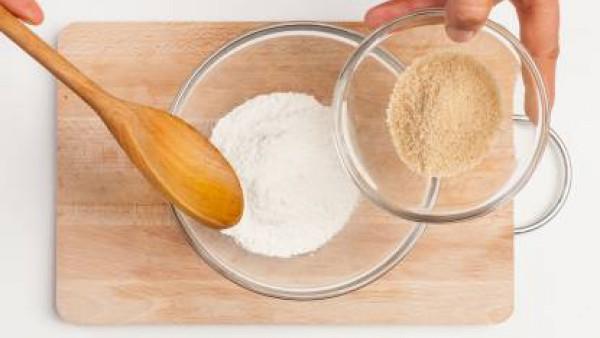 En un bol, coloca la harina, vierte el azúcar, añade los huevos y la mantequilla derretida. Remueve bien la mezcla y agrega la ralladura de la naranja y 1 taza de manzanilla.
