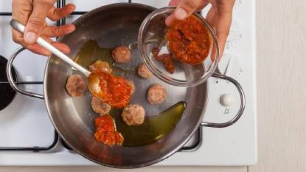 En una sartén, dora las albóndigas en 1 cucharada de aceite de oliva. Añade el tomate frito y termina de cocinar.
