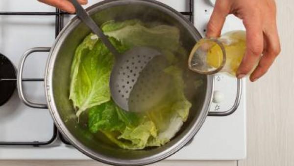Quita las hojas exteriores de la col, lávalas y separa las hojas interiores de una en una. Cuece durante 10 minutos en una olla grande con el caldo.