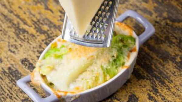 Unta ligeramente con aceite de oliva virgen extra los moldes y llénalos con el pan, la col y el queso. Espolvorea con queso rallado y hornea a 180 ° C durante 10 minutos. Sirve caliente.