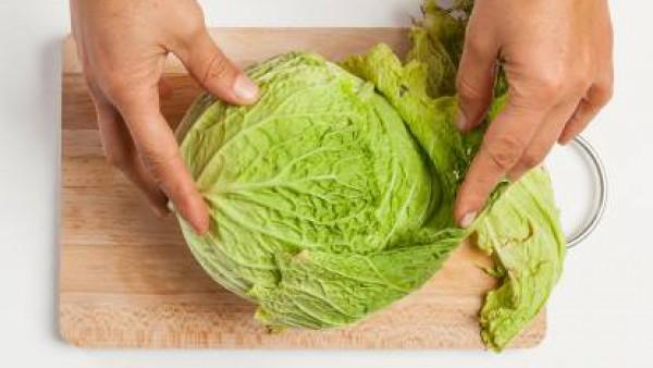 Lava la col, después de quita las hojas exteriores; y córtala en tiras. Machaca el ajo y pela las patatas.