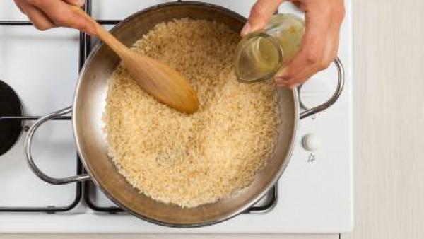 Pela y pica la cebolla. En una sartén grande, dórala en 1 cucharada de aceite de oliva virgen extra. A continuación, añade el arroz y deja asar por un tiempo. Vierte el 1 vaso Caldo Casero de Verduras