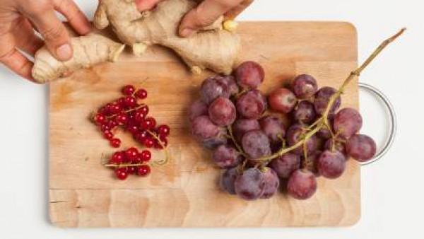 Pela el jengibre, rállalo y exprime el jugo. Lava y limpia la fruta; separa las semillas de la granada de las bayas, pela la uva. Exprime el jugo de medio limón. Por separado, hierve una taza de agua