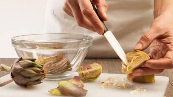 Limpia las alcachofas quitando las hojas exteriores. Con un cuchillo elimina también la barba interna y corta en trozos.