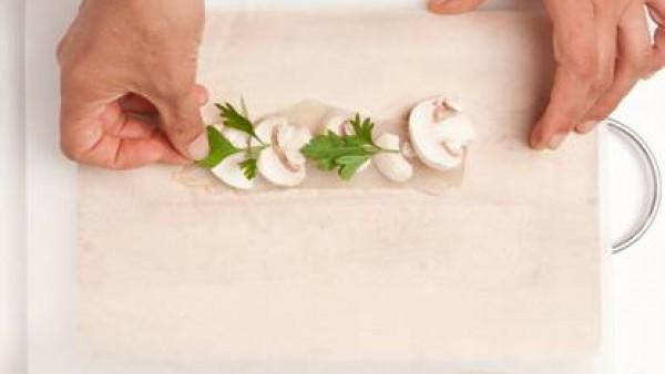 Prepara los cartuchos con los filetes de pescado, las setas, las hojas de perejil y baña con el caldo. Cuece en el horno a 180 grados durante 15 minutos.