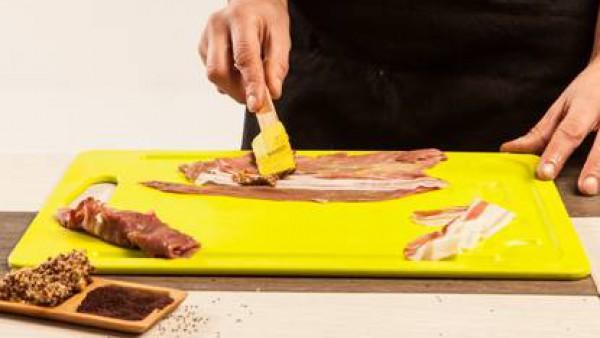 Coloca los filetes de ternera sobre una tabla de cortar y cepíllalos con las semillas de mostaza. Pon sobre cada uno de ellos una loncha de panceta.