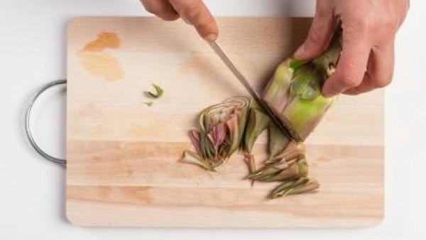 Limpia las alcachofas, córtalas en rodajas y se fríelas en un wok con aceite de oliva y el diente de ajo.