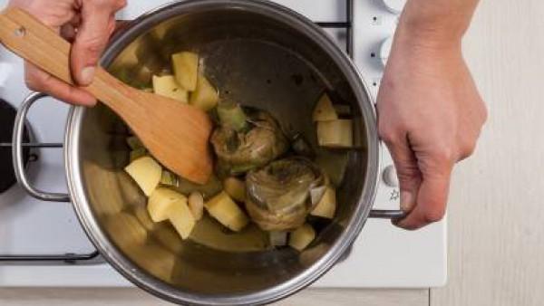 Pela las patatas y córtalas en trozos. Limpia las alcachofas y fríelas en una sartén con un poco de aceite de oliva. A continuación, añade el caldo y, después de 15 minutos de cocción, añade las patat