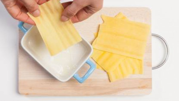 Engrasa ligeramente un molde para hornear, prepara el plato alternando placas de lasaña, bechamel y la mezcla de guisantes.