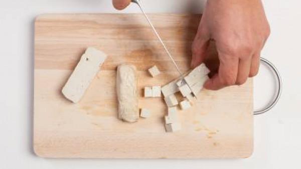 Corta el tofu en dados. Pon la cebolla en una sartén con aceite de oliva, añade el tofu y fríelo durante 5-6 minutos.