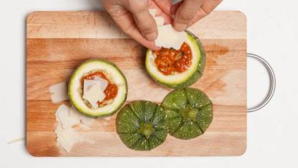 En un bol, corta la carne de los calabacines con la menta y la albahaca. Añade el cuscús y mezcla bien. Rellena los calabacines con la mezcla.