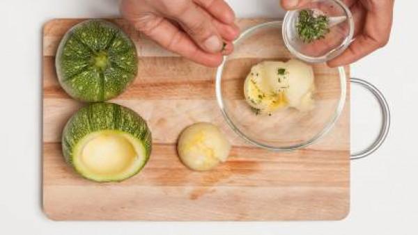 Vacía los calabacines redondos, tritura el interior de los calabacines junto con un diente de ajo y perejil. Añádele el huevo y el pan rallado, mezclar bien y sazona con pimienta.
