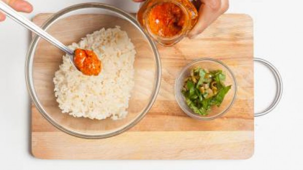 Escurre el arroz y pásalo por agua fría para hacerle perder todo el almidón, añade las aceitunas y albahaca picadas y las cucharadas de sofrito. Rellena los pimientos, unta con aceite, espolvorea con