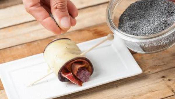 Da forma a los rollitos, sujétalos con un pincho y decora con semillas de amapola.