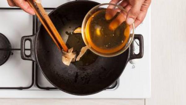 Dora en un wok el diente de ajo con una cucharada de aceite de oliva y añade las setas hidratadas.